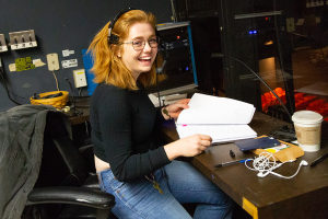 Katie Stevenson sits at a cluttered stage manager's desk in a theater control room, wearing a headset.