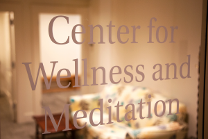 A glass door with the text 'Center for Wellness and Meditation'