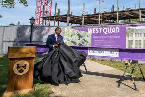 """President Sean Decatur pulls a black curtain off of a purple steel beam, revealing the text """"Chalmers Library."""""""