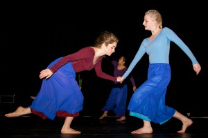 Two dancers interact in a choreographed piece, with a third dancer in the background.