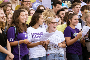 Smiling new students gather in front of Rosse Hall for the First-Year Sing, holding sheet music.