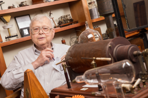 Professor Thomas Greenslade poses with his collection of physics apparatus.