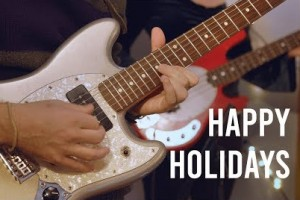 "An image of a hand playing an electric guitar, with the text ""Happy Holidays"""