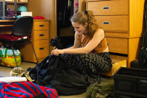 A young woman unpacks a bag while kneeling on the floor of a new dorm room.