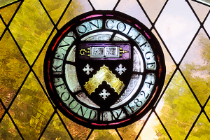 The seal of Kenyon College rendered in stained glass.