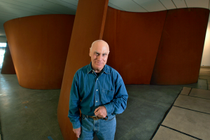 The artist Richard Serra, wearing a blue shirt and blue jeans, poses in front of one of his large steel sculptures.