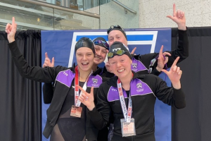 Four swimmers on a 1st-place podium