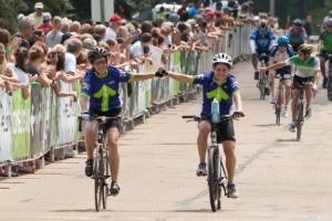 Two bicyclists wearing purple Kenyon jerseys hold hands as they cross a finish line.
