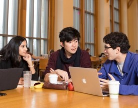 A group of students talk at a dining room table.