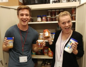 Two students pose with jars of peanut butter