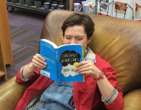 A girl sits in a chair reading a book.