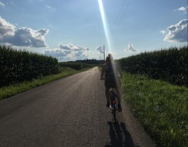 Student cycling through fields