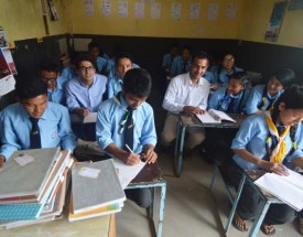 A group of students sit in a Nepalese classroom.