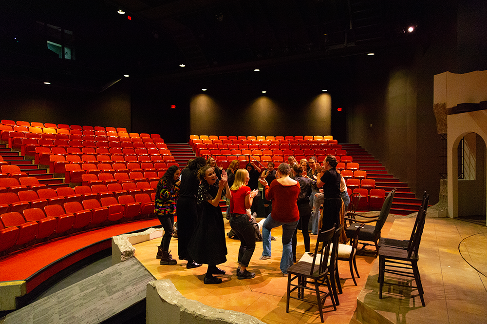 Actors dancing in a circle on stage